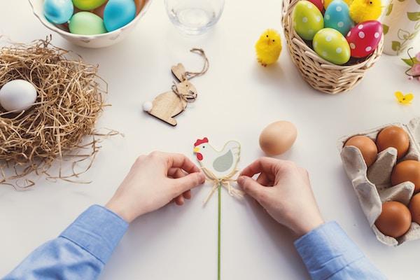 Zwei Hände binden einer Huhnholzfigur eine Schleife um | Sieh an Gutschein