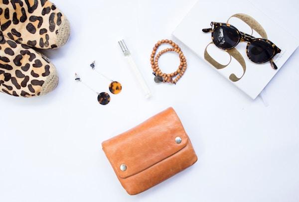 Schmuck und Handtasche und Sonnenbrille liegen verstreut auf einem weißen Tisch | Sieh an Gutschein