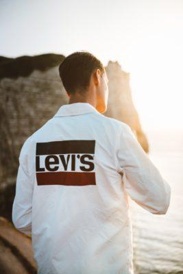 Ein junger Mann mit einer weißen Jacke auf der das Logo von Levi's zu sehen ist | Rabatte Coupon