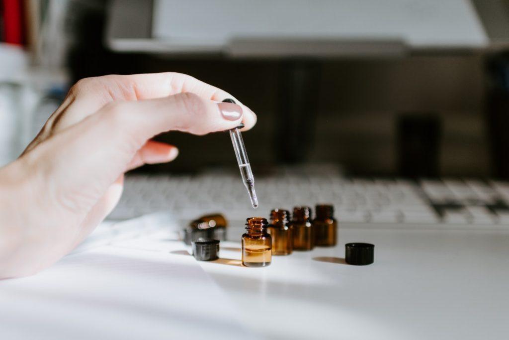 Eine mit Flüssigkeit gefüllte Pipette auf einem Tisch mit kleinen Fläschchen | Rabattcoupon
