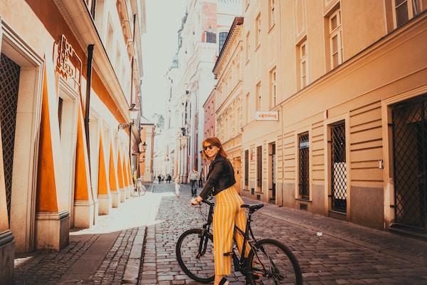 Eine junge hübsche Frau beim Fahrrad fahren   Rabatt-Coupon