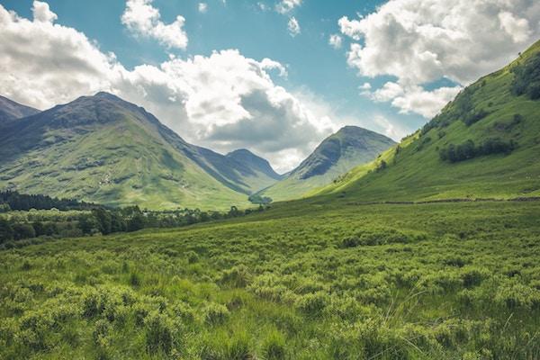 Ein Gebirge mit viel grünem Gras   Rabatte Coupons