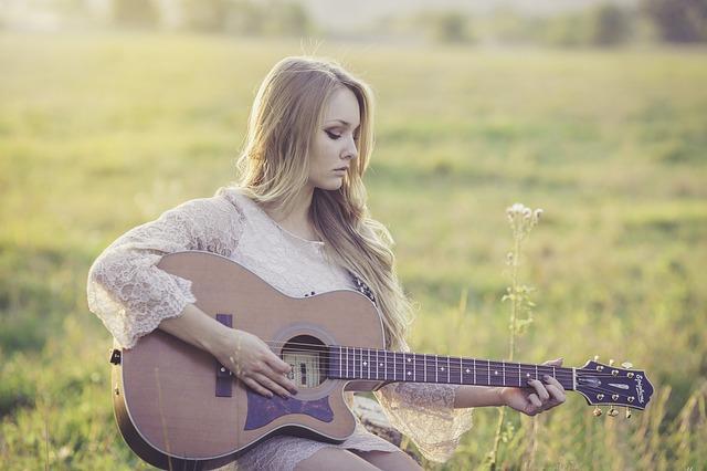 Eine hübsche junge Dame mit einer Gitarre | Rabatte Coupons