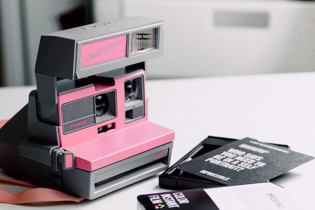 Eine pinke Polaroid die auf dem Tisch liegt | Rabatt Coupons