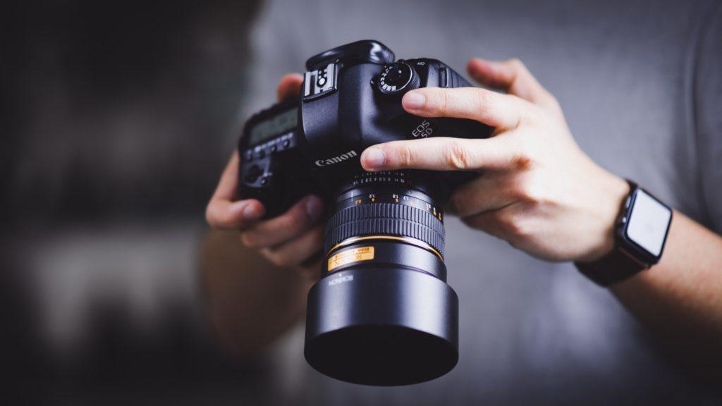 Eine Person hält eine Kamera in der Hand | Rabatte Coupons