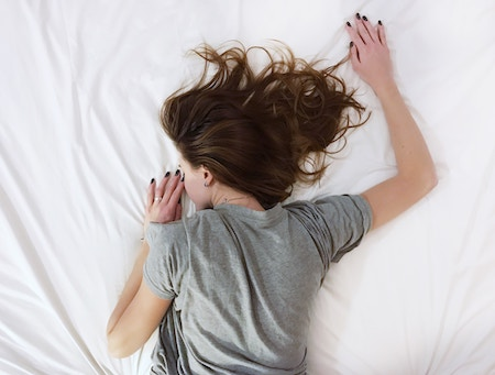 Eine Frau liegt im Bett und schläft | Rabatte Coupons