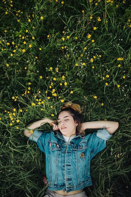 Eine Frau schläft auf der Wiese | Rabatte Coupons
