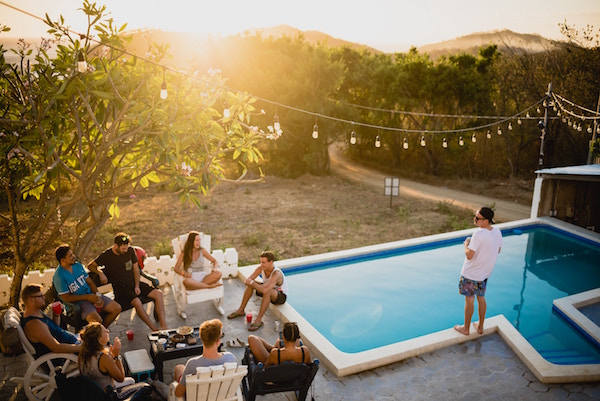 Fröhliche Personen sitzen neben einem Pool   Rabatt-Coupon