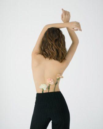 Eine Frau die mit dem Rücken zur Kamera zeigt. Ebenso sind drei Blumen zu sehen | Rabatte Coupons