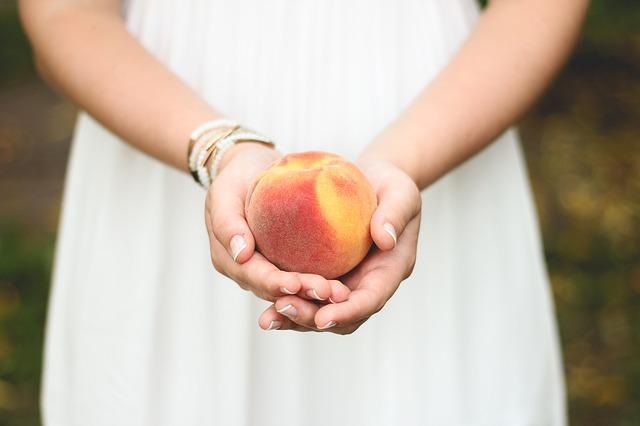 Ein frischer Pfirsich in Händen einer Frau | Rabattcoupons