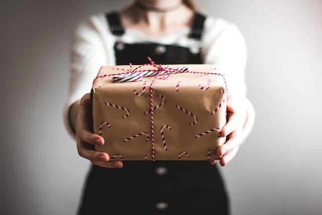 Eine Frau überreicht ein Weihnachtsgeschenk | rabatte coupons