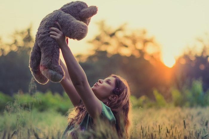 Mädchen, dass voller Euphorie einen Teddy in die Luft hält | rabatt coupons