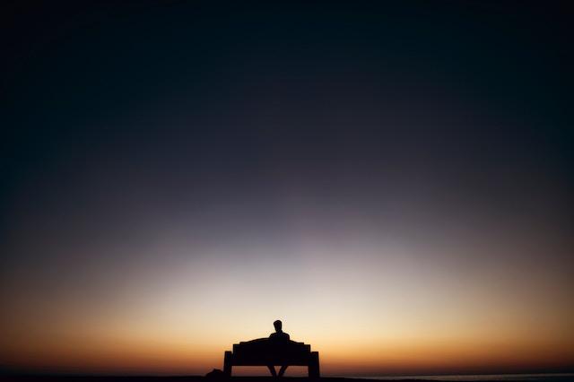 Ein Single der alleine dem Sonnenuntergang zusieht