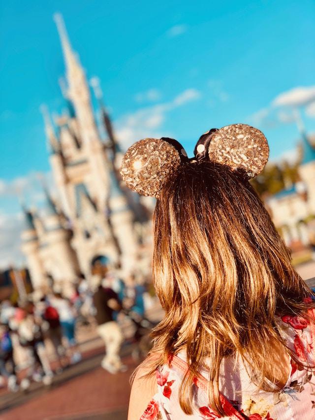 Mädchen steht vor Disneyschloss