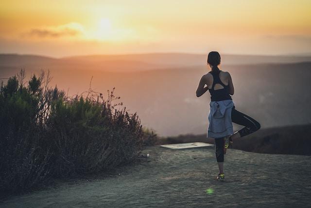 Eine Frau im Sonnenuntergang beim Yoga | rabatte coupons