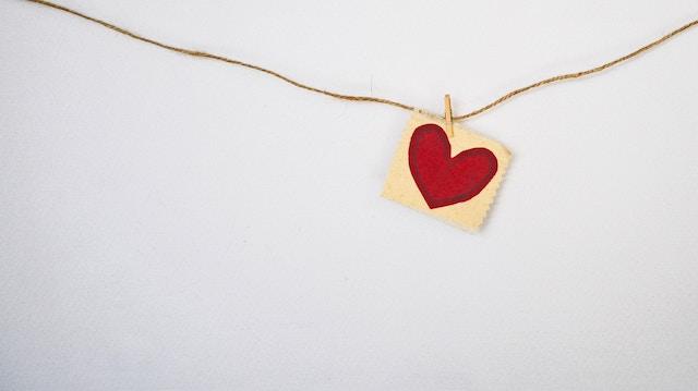 Ein kleines rotes Herz hängt an einer Schnur auf einem weißen Hintergrund | rabatte coupons