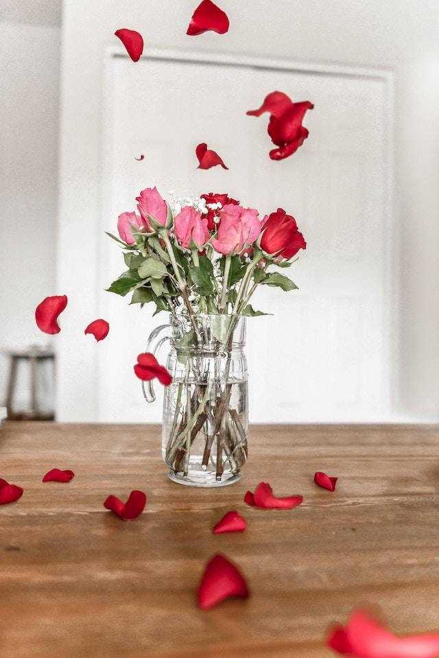 Ein Blumenstrauß rosa-roter Rosen steht auf einem Holztisch in einer Glasvase | rabatte coupons