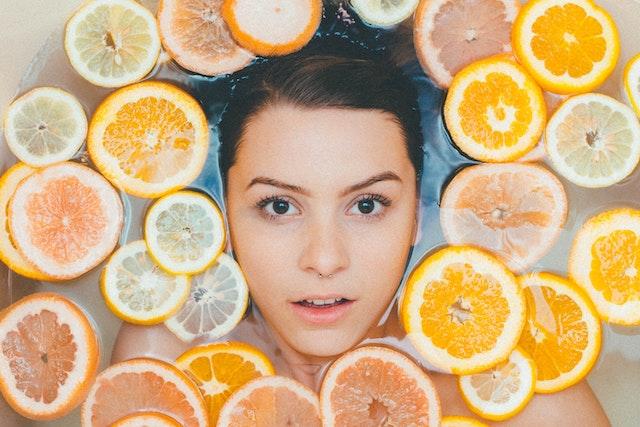 Ein weibliches Gesicht mitten in Orangen- und Zirtonenscheiben | BLATTKULTUR Gutscheincode