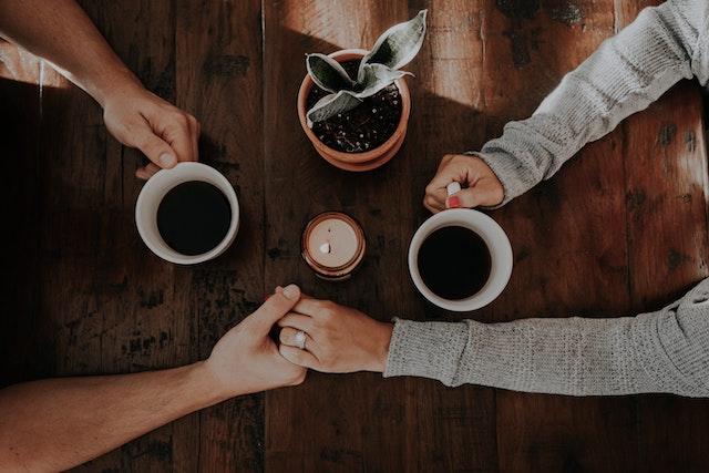 Ein Paar sitzt an dem Tisch und hält sich an den Händen mit einem Kaffeebecher in der anderen Hand | Audible Gutschein