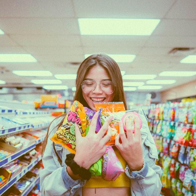 Eine Frau mit ganz vielen Süßigkeiten in beiden Händen   rabatte coupons
