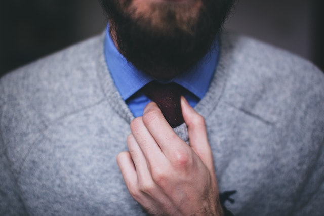 Ein Mann mit Hemd und Krawatte greift sich an die Krawatte | rabatte coupons