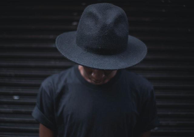 Ein dunkel gekleideter Mann mit einem schwarzen Hut | rabatte coupons