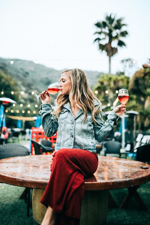 Eine Frau mit zwei Weingläsern in der Hand   rabatte coupons