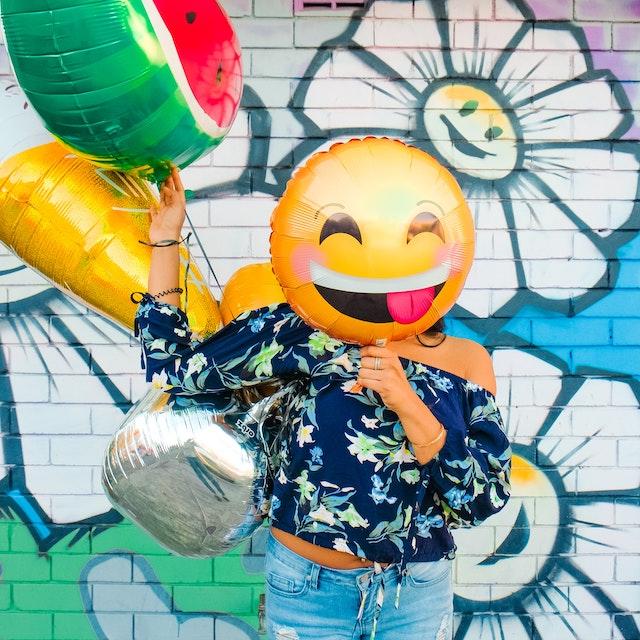 Eine Frau hält sich einen lachenden Luftballon vor das Gesicht   rabatte coupons